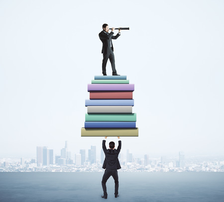 Businessman holding book stack with colleague looking into the distance with telescope on blurry city background. Education and vision concept Stok Fotoğraf