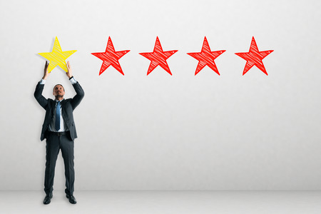 Young businessman on concrete background with five star rating. Ranking and feedback concept