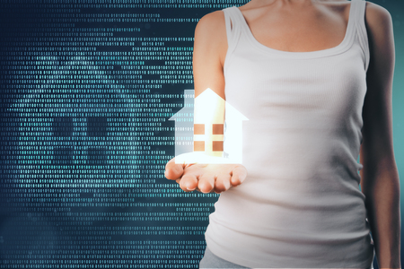 Female hand holding abstract home icon on binary code background. Smart home and software concept. Double exposure