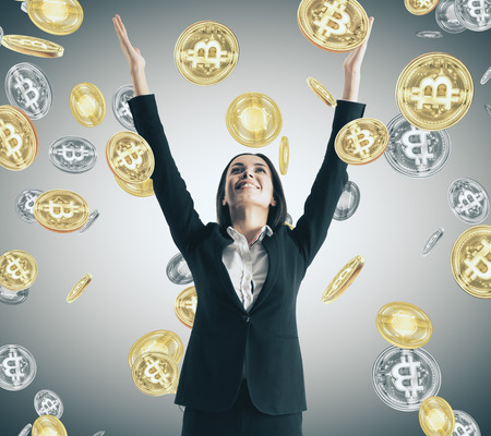 Happy young businesswoman with bitcoin rain. Lottery win and trade concept Archivio Fotografico - 112735784