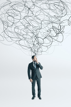 Thoughtful young businessman with scribble standing on white background. Confusion and solution concept Stock Photo