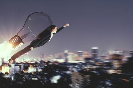 Side view of young super hero businesswoman flying with launching rocket on blurry night city background. Confidence and innovation concept