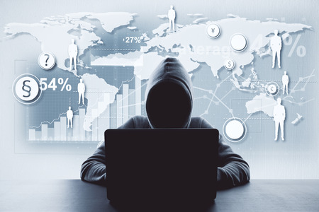 Unrecognizable hacker using computer with digital business interface. Hacking and data concept