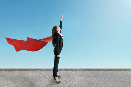 Young european superhero businesswoman with red cape standing on rooftop with sky background. Success and leadership concept