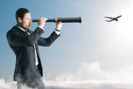 Businessman looking at airplane with telescope. Research and vision concept