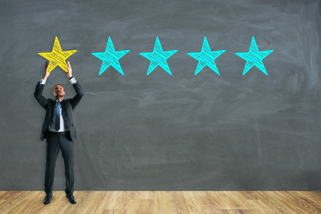 Young businessman on chalkboard background with five star rating. Ranking and appraisal concept