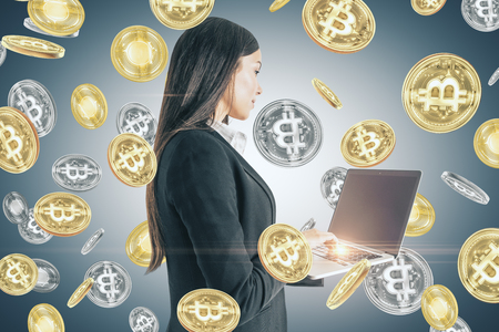 Attractive young businesswoman with bitcoin rain and laptop. Lottery win, technology and trade concept Archivio Fotografico - 112735883