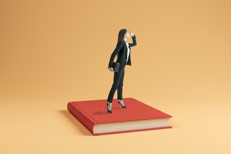 Attractive young businesswoman looking into the distance while standing on book. Education and knowledge concept. Stok Fotoğraf