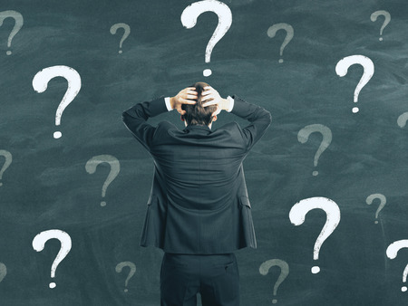 Back view of young businessman on chalkboard wall background with question marks. Confusion and think concept Stock Photo