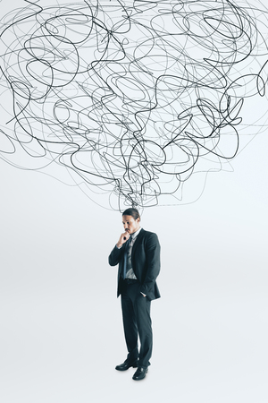Thoughtful young businessman with scribble standing on white background. Confusion and doubt concept