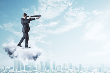 Side view of young businessman on cloud using telescope to look into the distance on bright blue sky background. Vision and job concept