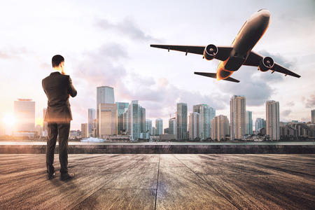 Young businessman on rooftop looking at flying airplane on sky and city background. Travel and passenger concept Stock Photo