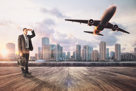 Young businessman on rooftop looking at flying airplane on sky and city background. Vision and passenger concept