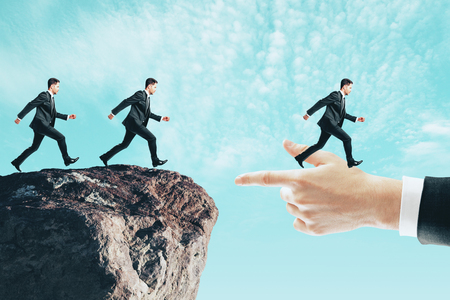 Businessmen running to hand from cliff. Teamwork and connection concept Stock Photo