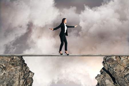 Young businesswoman balancing between two cliffs on cloudy sky background. Equilibrium concept