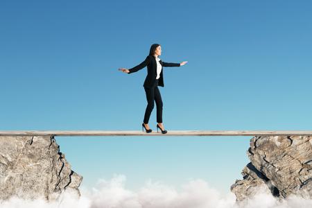 Junge Geschäftsfrau, die zwischen zwei Klippen auf Hintergrund des blauen Himmels balanciert. Gleichgewichtskonzept