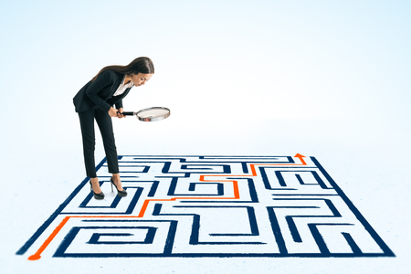 Attractive young european businesswoman using magnifier to look at maze on ground. Challenge and solution concept Фото со стока