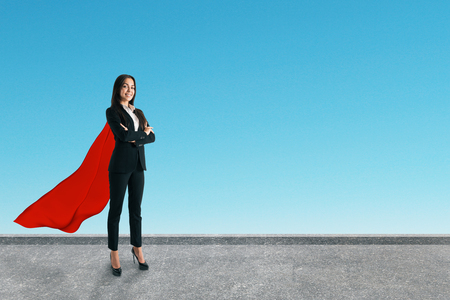 Young european superhero businesswoman with red cape standing on rooftop with sky background. Success and strength concept Stockfoto