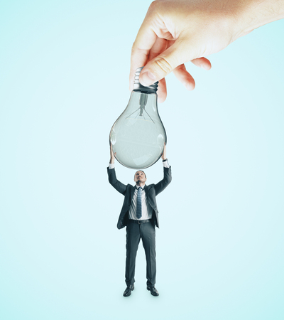 Hand handing lamp to businessman on blue background. Idea and teamwork concept