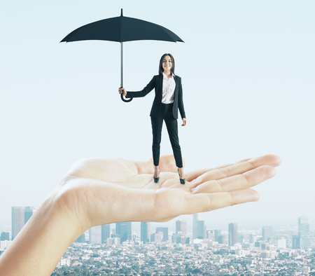 Abstract hand holding european businesswoman with umbrella on city background. Success and protection concept