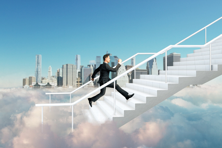 Side view of young businessman climbing abstract cloud stairs on blue sky city background. Success and growth concept