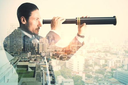 Side view of young businessman using binoculars to look into the future on abstract city background. Vision and success concept. Double exposure Stockfoto