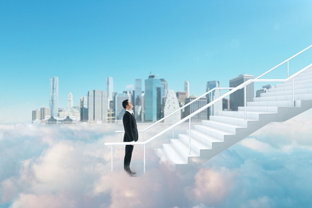 Side view of young businessman climbing abstract cloud stairs on blue sky city background. Success and heaven concept