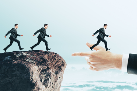 Businessmen running to hand from cliff. Teamwork and challenge concept
