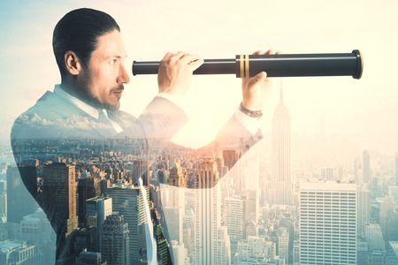 Side view of young businessman using binoculars to look into the future on abstract city background. Vision and research concept. Double exposure
