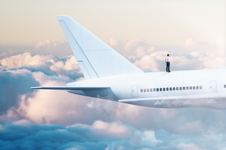 Young businessman looking into the distance while standing on white airplane in blue sky. Research and travel concept.