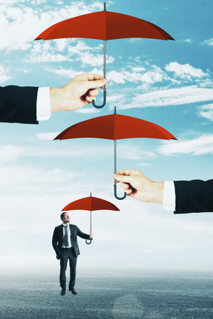 Abstract image of businessman with several umbrellas. Security and finance concept Imagens
