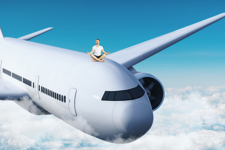 Young man meditating on airplane. Sky background. Freedom and transport concept.