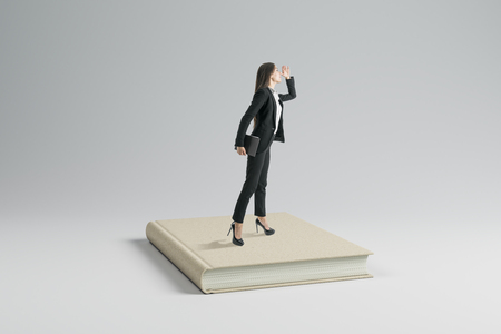 Attractive young businesswoman looking into the distance while standing on book. Education and vision concept.