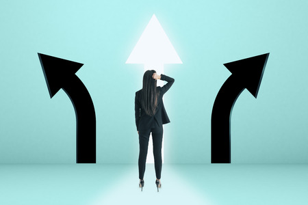 Young businesswoman with arrow choice on blue background. Different direction and path concept Stok Fotoğraf