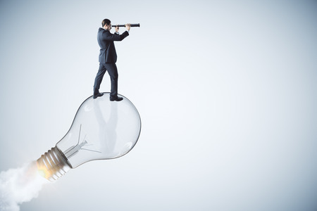 Side view of young businessman using binoculars on abstract launching lamp. Startup, idea and vision concept.