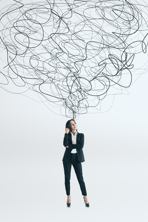 Thoughtful young businesswoman with scribble standing on white background. Confusion and solution concept