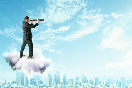 Side view of young businessman on cloud using telescope to look into the distance on bright blue sky background. Vision and opportunity concept