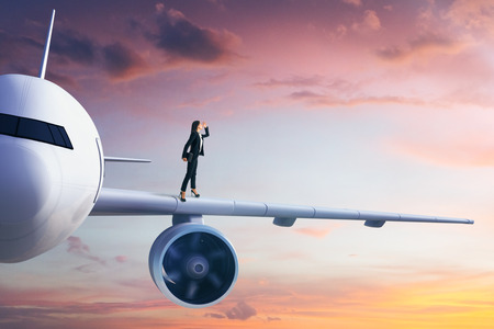 Side view of young european businesswoman looking into the distance while standing on white airplane in blue sky. Transportation and travel concept.