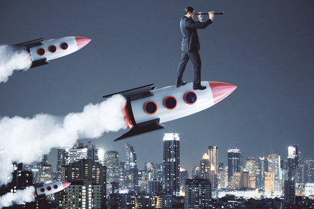 Businessman using telescope while standing on launching rocket. City background. Future and startup concept 版權商用圖片