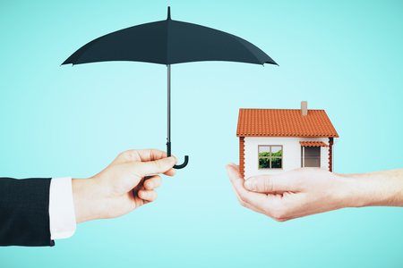 Hands holding house and umbrella on sky background. Real estate and assuarance concept Stock Photo