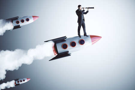 Businessman using telescope while standing on launching rocket. Gray background. Vision and startup concept