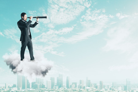 Side view of young businessman on cloud using telescope to look into the distance on bright blue sky background. Vision and future concept