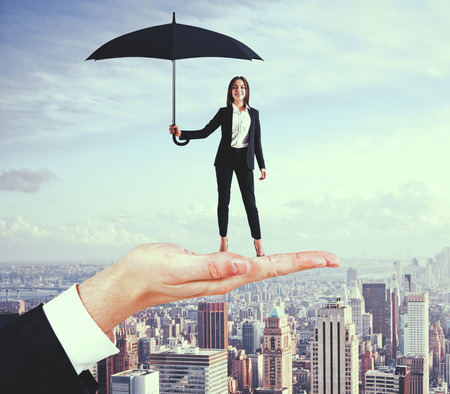 Abstract hand holding pretty businesswoman with umbrella on city background. Success and protection concept