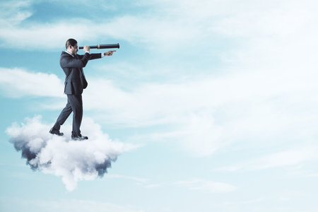 Side view of young businessman on cloud using telescope to look into the distance on bright blue sky background. Vision and success concept