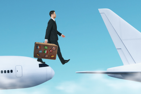 Side view of young businessman with luggage jumping from plane to plane. Challenge and trip concept Stock Photo