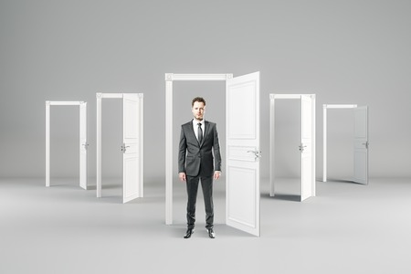 Businessman in abstract interior with open doors. Opportunity and future concept. Banco de Imagens - 113329883