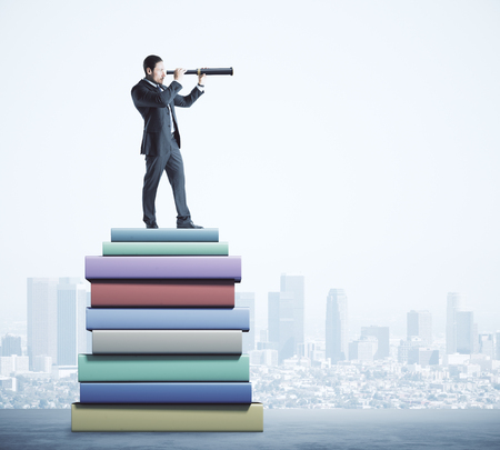 Attractive young european businessman using telescope while standing on pile of books on blurry city background. Education and vision concept.
