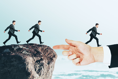 Businessmen running to hand from cliff. Teamwork and risk concept