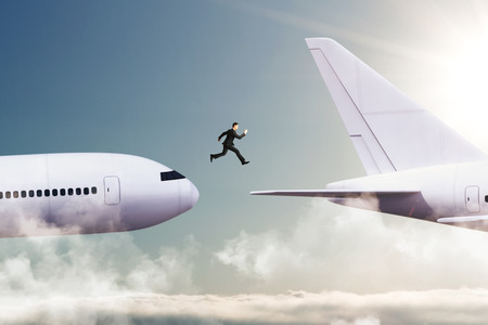 Side view of young businessman jumping from plane to plane. Challenge and travel concept Banque d'images - 113329895