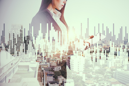 Side view of beautiful young european businesswoman using tablet on abstract city background with forex chart. Technology and investment concept. Double exposure
